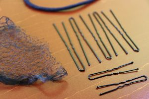 Supplies to Create a Sculptured Bun with Locs including a hair net, hair pins, and hair tie.